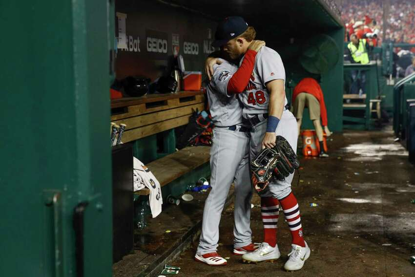 St. Louis Cardinals' Oliver Marmol and Harrison Bader embrace after Game 4 of the baseball National League Championship Series against the Washington Nationals Tuesday, Oct. 15, 2019, in Washington. The Nationals won 7-4 to win the series 4-0. (AP Photo/Patrick Semansky)