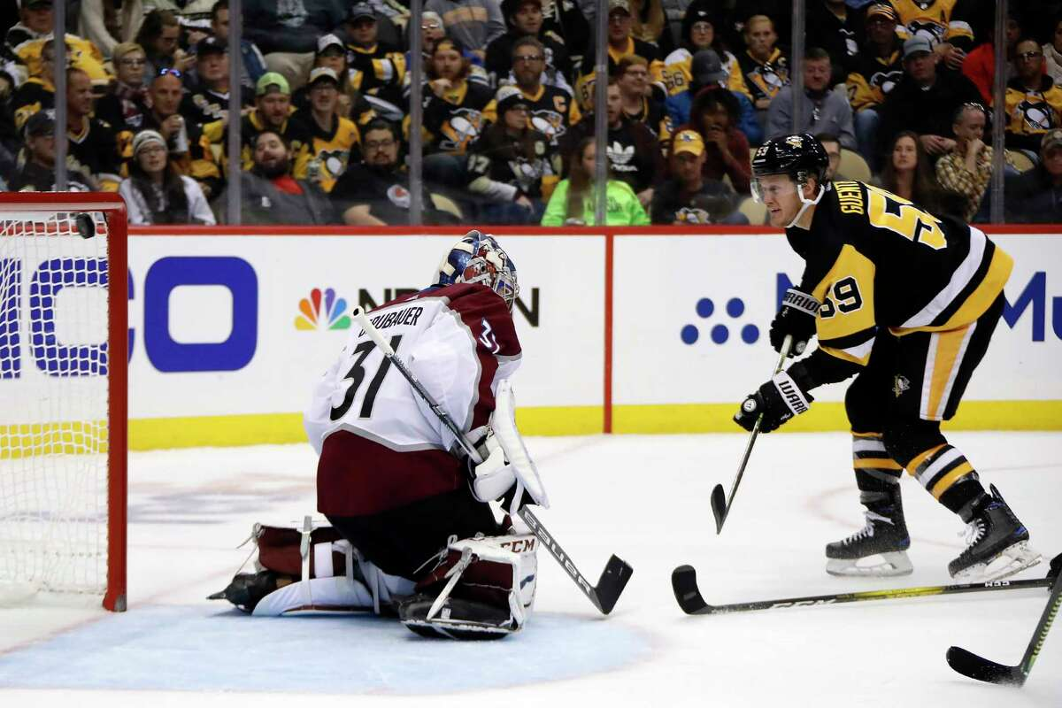 Pittsburgh Penguins' Jake Guentzel (59) scores against Colorado Avalanche goaltender Philipp Grubauer (31) during the second period of an NHL hockey game in Pittsburgh, Wednesday, Oct. 16, 2019. (AP Photo/Gene J. Puskar)
