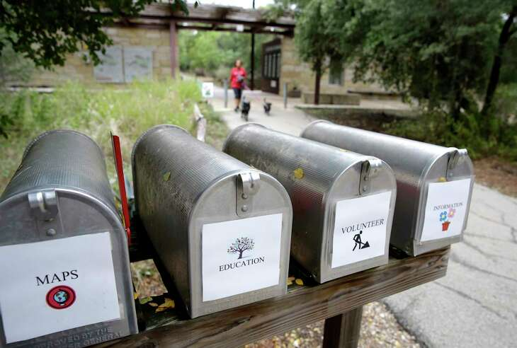 Information mailboxes line a path in Phil Hardberger Park where Carolyn Miller walks her dogs Cookie and Bama every day.
