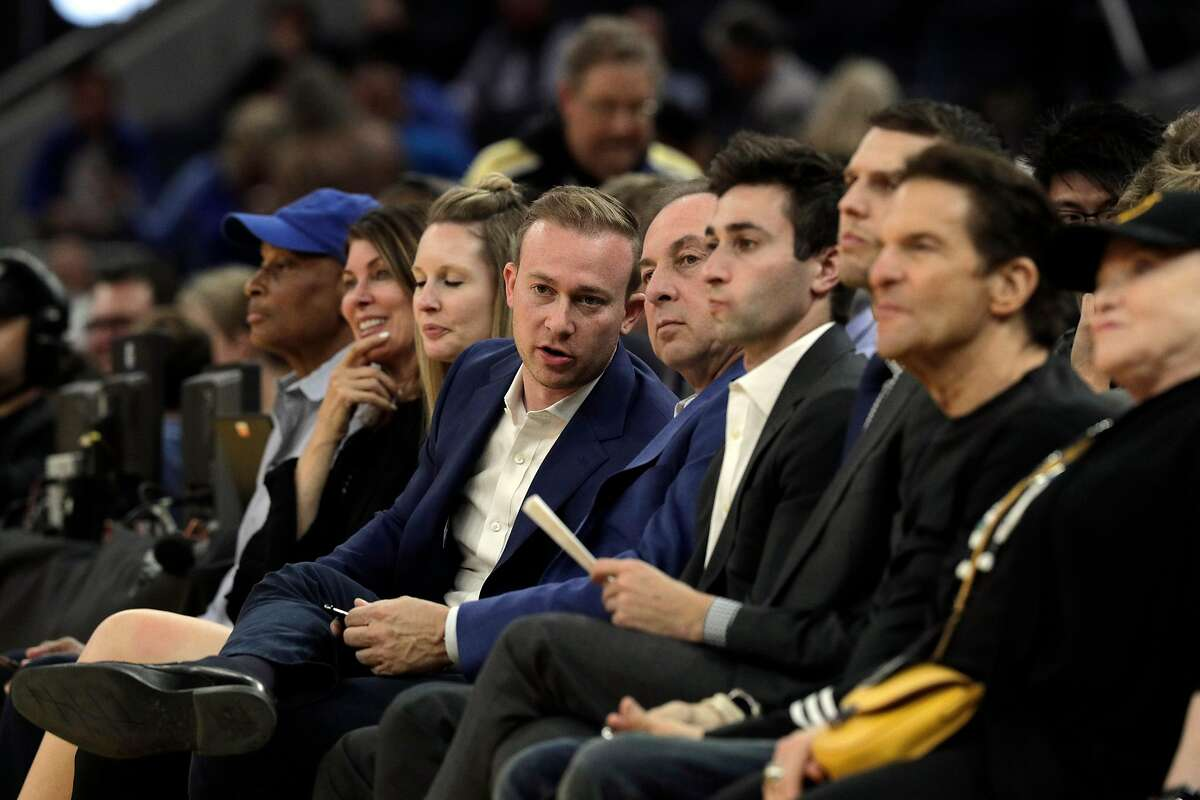 Kirk Lacob talks to his father Joe Lacob on the sidelines as they watch the game in the first half as the Golden State Warriors played the Los Angeles Lakers in a pre-season game at Chase Center in San Francisco, Calif., on Saturday, October 5, 2019.