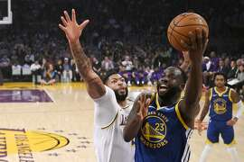 Golden State Warriors forward Draymond Green, right, shoots as Los Angeles Lakers forward Anthony Davis defends during the first half of a preseason NBA basketball game Wednesday, Oct. 16, 2019, in Los Angeles. (AP Photo/Mark J. Terrill)