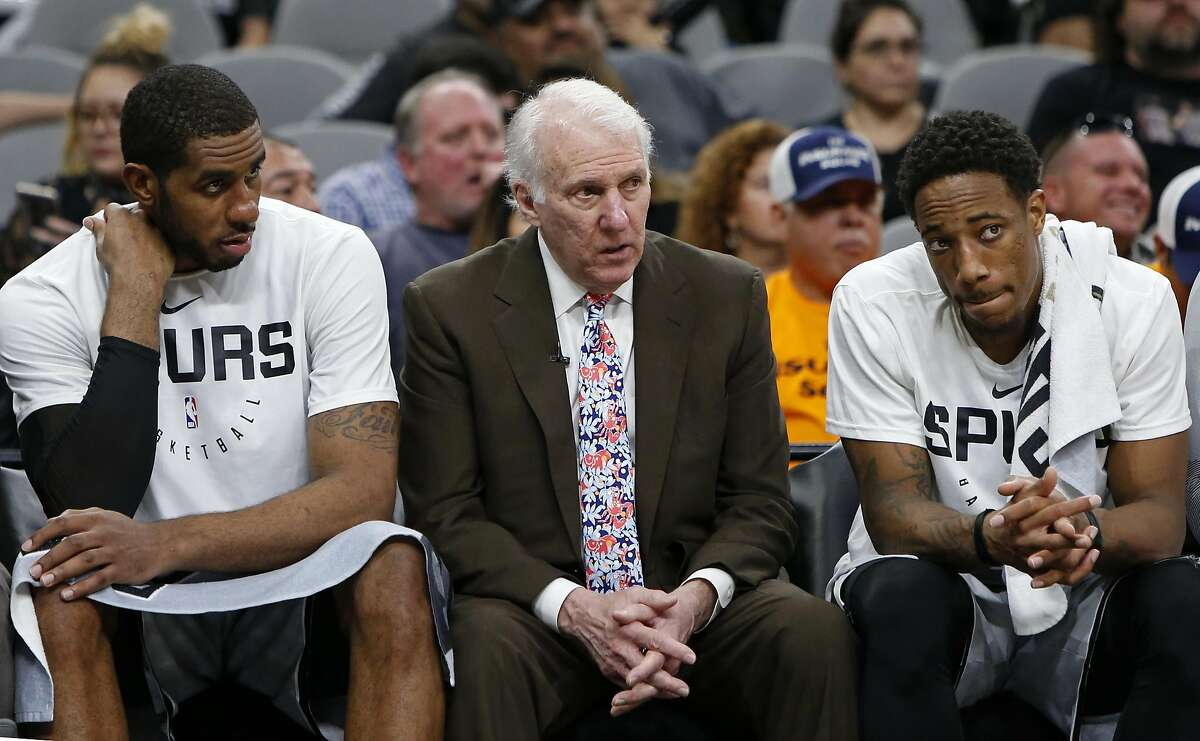 SAN ANTONIO, TX - NOVEMBER 30: Gregg Popovich head coach of the San Antonio Spurs talks with players LaMarcus Aldridge #12, and DeMar DeRozan #10 on the bench during an NBA game against the Houston Rockets held November 30, 2018 at the AT&T Center in San