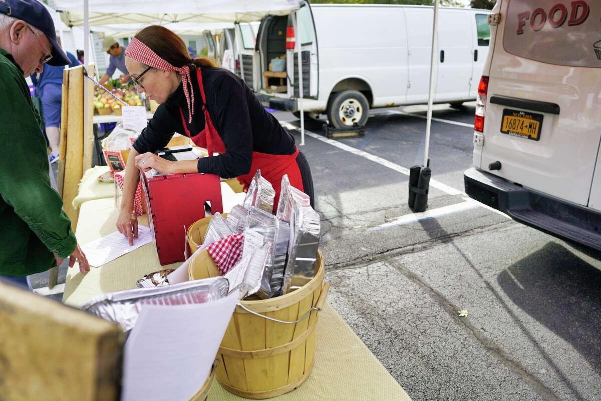 Trisha Nusbaum, owner of Food Florist, goes over a menu with a customer at the Delmar Farmers Market on Tuesday, Oct. 8, 2019, in Delmar, N.Y. (Paul Buckowski/Times Union)