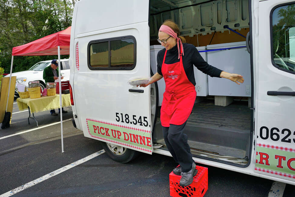 Trisha Nusbaum, owner of Food Florist, brings one of her frozen dishes out to a customer at the Delmar Farmers Market on Tuesday, Oct. 8, 2019, in Delmar, N.Y. (Paul Buckowski/Times Union)
