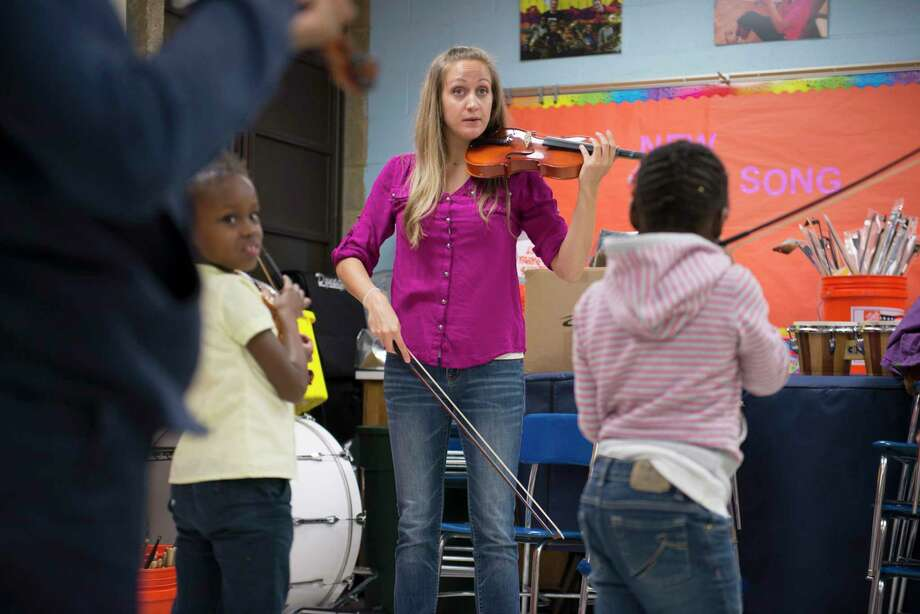 Lauren Rausch teaches a classroom of youngsters how to play the violin at Lockerman Bundy Elementary School in Baltimore in 2013. Photo: Washington Post Photo By Marvin Joseph / The Washington Post