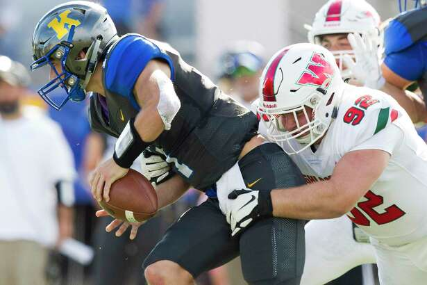 The Woodlands defensive linemen Alex Henwood (92) wraps up Klein quarterback Bryce Corriston (11) during the fourth quarter of a District 15-6A high school football game at Klein Memorial Stadium, Saturday, Oct. 12, 2019, in Spring.