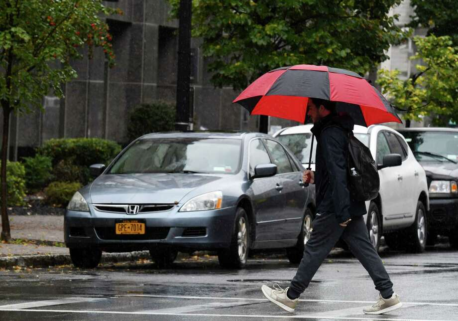 Umbrella cover held back the rain for this pedestrian crossing Broadway on Thursday, Oct. 17, 2019, in Albany, N.Y.  (Will Waldron/Times Union) Photo: Will Waldron, Albany Times Union