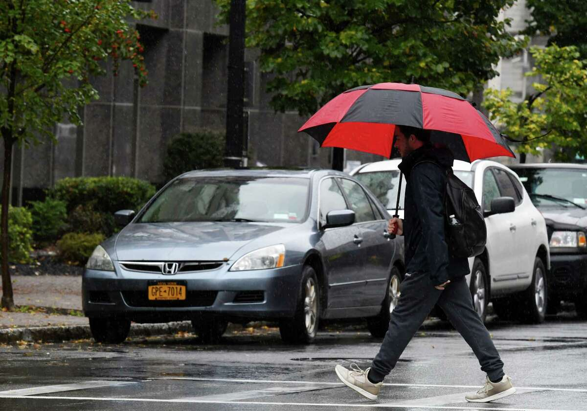 Umbrella cover held back the rain for this pedestrian crossing Broadway on Thursday, Oct. 17, 2019, in Albany, N.Y. (Will Waldron/Times Union)
