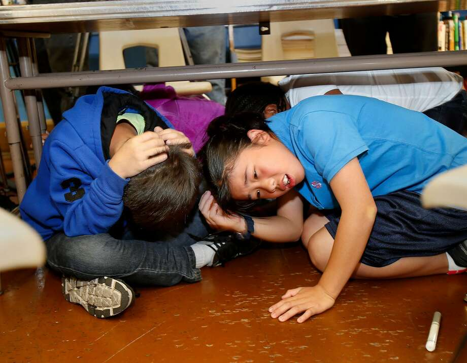 "Sixth graders Susan Li (right) and her classmate Victor Ruan ducked under their classroom table for the earthquake drill Thursday October 16, 2014. The great California ""Shakeout"" was observed at Marina Middle School in San Francisco, Calif. with an earthquake drill for students and some public officials. Photo: Brant Ward / The Chronicle"