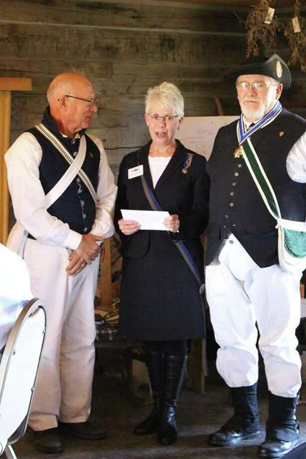 Eric Reelitz, left, and Robert Ridenour, right, accept a $600 check from Leah Beckoff, president of the Illinois Society USD1812, to help maintain Hill's Fort.