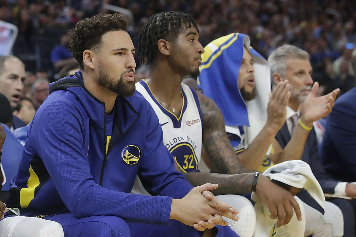 Injured Golden State Warriors guard Klay Thompson, from left, Marquese Chriss and Stephen Curry watch during the first half of a preseason NBA basketball game against the Los Angeles Lakers in San Francisco, Saturday, Oct. 5, 2019. (AP Photo/Jeff Chiu)