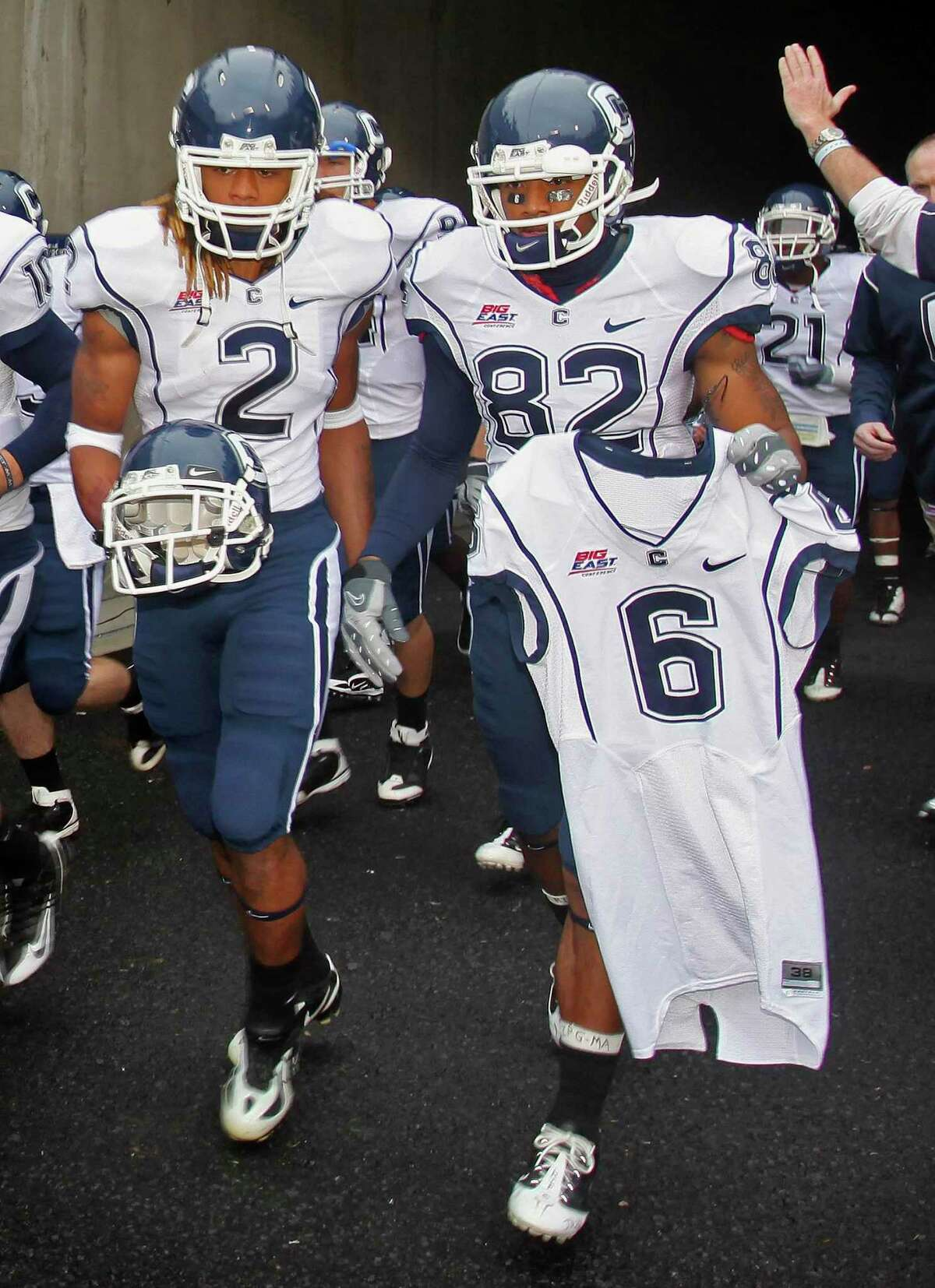 UConn's Andre Dixon (2) and Kashif Moore enter Mountaineer Field carrying the helmet and jersey of slain teammate Jasper Howard in 2009.