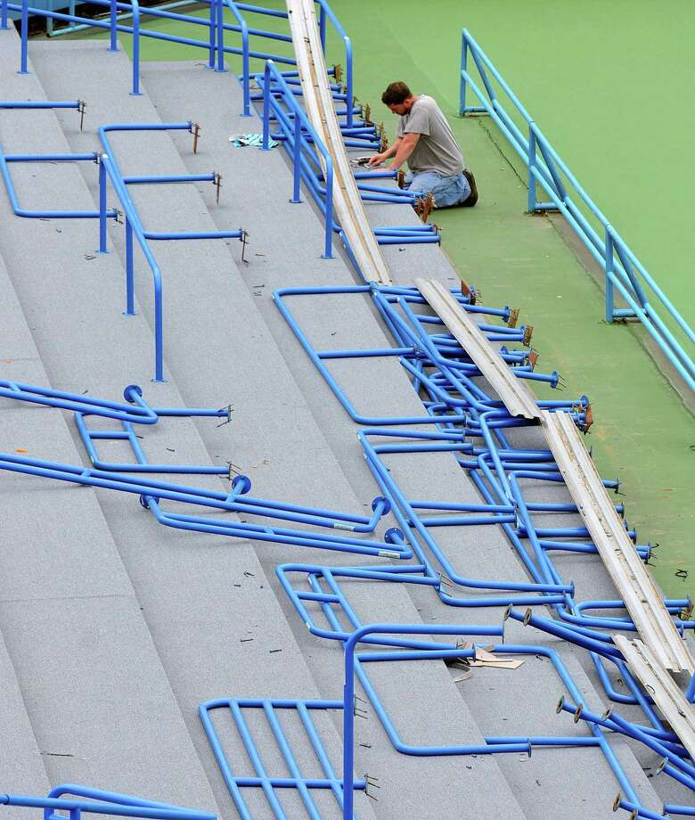 Peter Casolino — Register Installer Rob Torres works on replacing railings after installing all-weather carpeting in the Connecticut Tennis Center stadium court as workers were busy preparing for the upcoming New Haven Open at Yale. Torres works for Sullivan and Son Carpeting out of Hamden. The tennis tournament runs from runs from August 16 - 24. pcasolino@newhavenregister.com Photo: Peter Casolino
