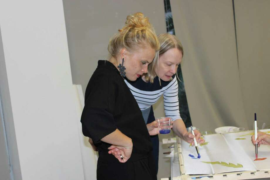 Instructor Inga Strause-Godejord guides student Zanda Brige in the art of painting on silk. Photo: Courtesy Photo