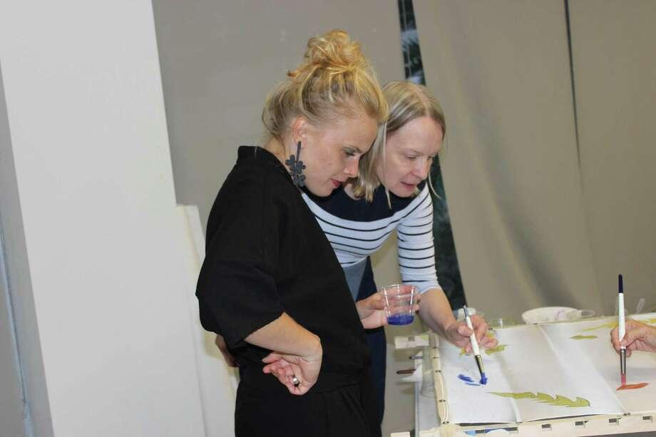 InstructorInga Strause-Godejord guides student Zanda Brige in the art of painting on silk. Photo: Courtesy Photo