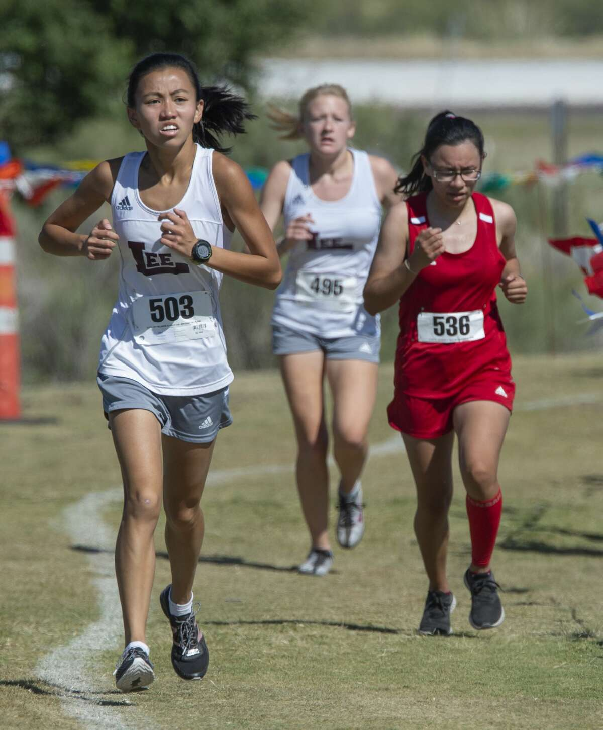 Lee's Hannah Long, front, runs the course 10/17/19 at the District 2-6A cross-country meet at UTPB Park in Odessa. Tim Fischer/Reporter-Telegram