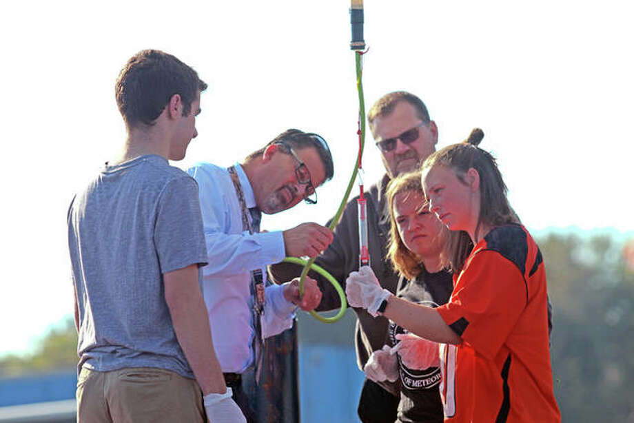 Edwardsville High School students Connor McNabnay, left; Makenzi Keller, Leah Griffin, both are far right; Edwardsville High Scool Assistant Principal Vince Schlueter, second from left; and parent Rick Goodwin prepare the weather balloon for launch earlier this month. Photo: For The Intelligencer