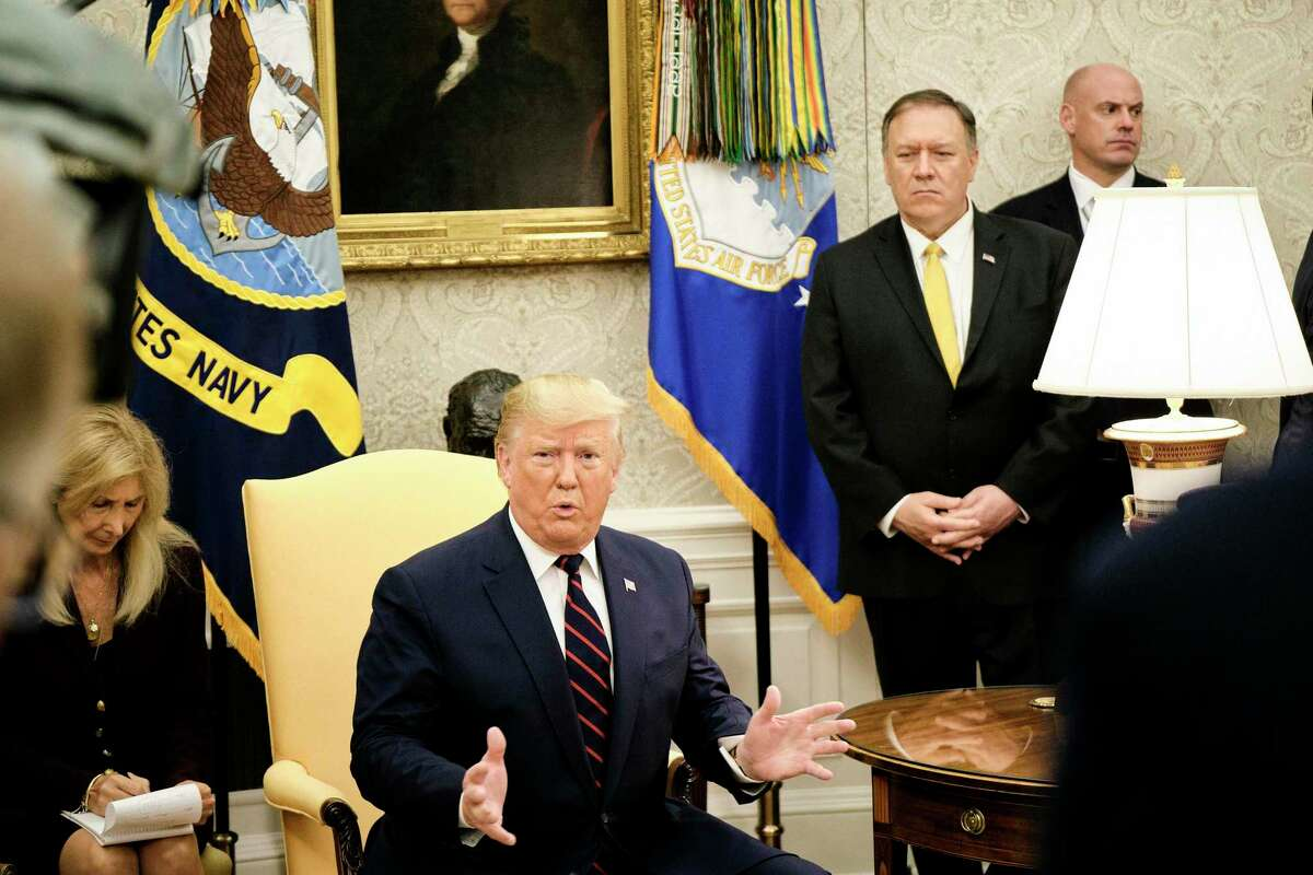 President Donald Turmp speaks to reporters, flanked by Secretary of State Mike Pompeo, ahead of a bilateral meeting with Italian President Sergio Mattarella in the Oval Office of the White House in Washington, Oct. 16, 2019. President Trump's trade truce with China may have temporarily cooled tensions between the world's two largest economies. But the damage from Trump's aggressive approach to trade policy will continue to weigh on the global economy. (T.J. Kirkpatrick/The New York Times)