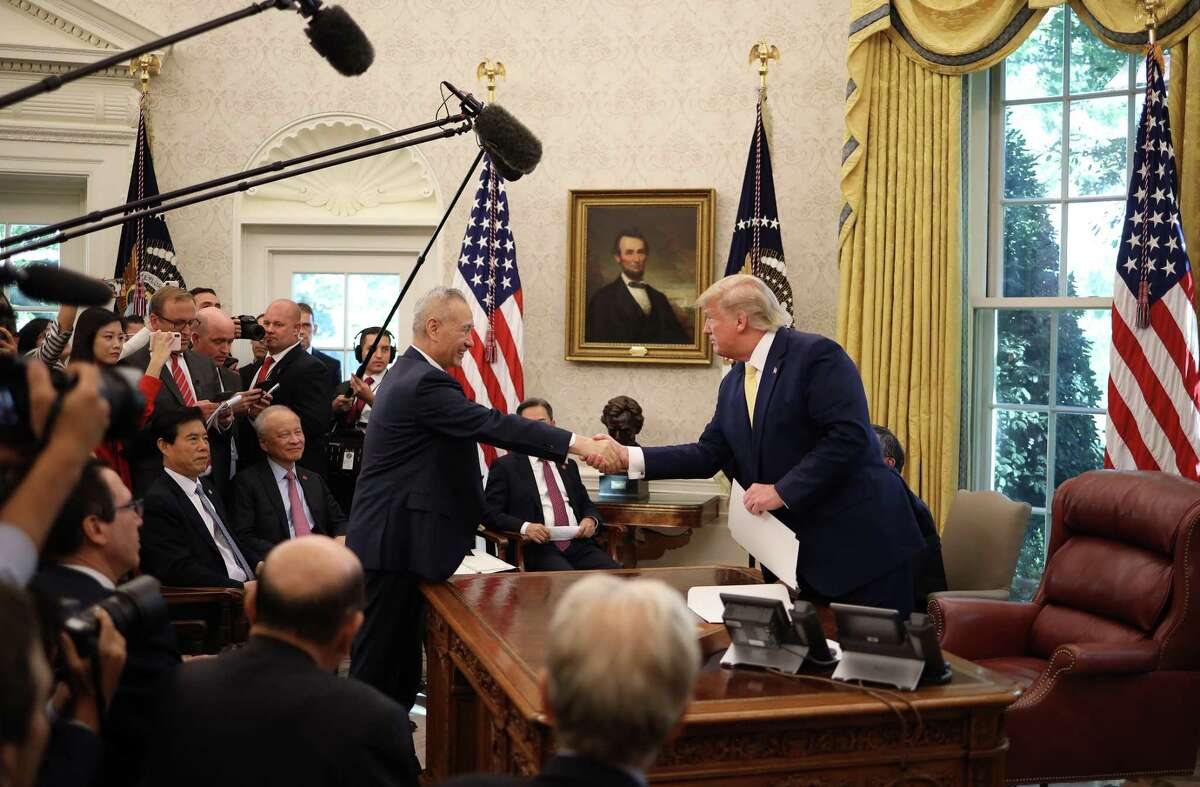 U.S. President Donald Trump shakes hands with Chinese Vice Premier Liu He after announcing a