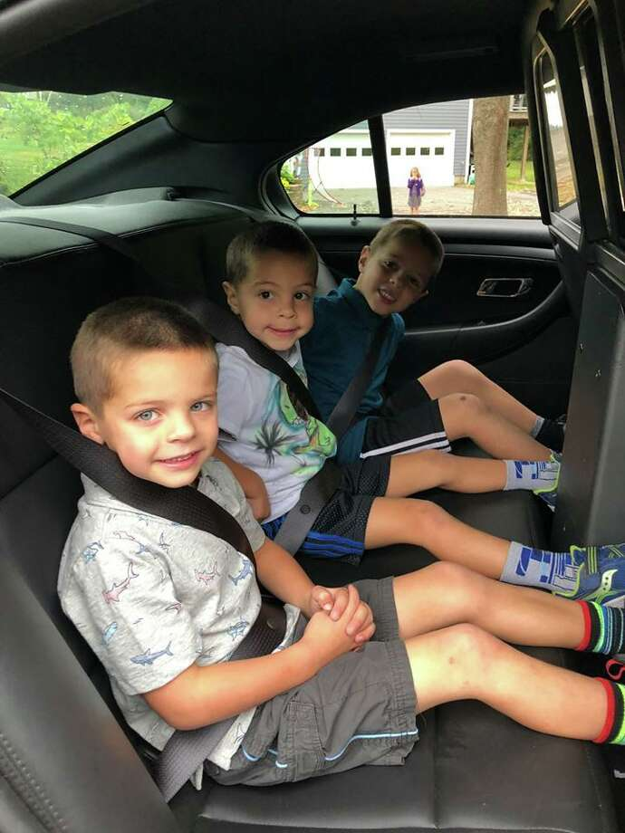 Veterans Park Elementary School students Charlie,Thomas and Henry Cannone won a ride to school with Ridgefield police officer Mark Giglio at the department's annual Cones and Cops event at Deborah Ann's Sweet Shoppe earlier this fall. Photo: Ridgefield Police Department / Facebook