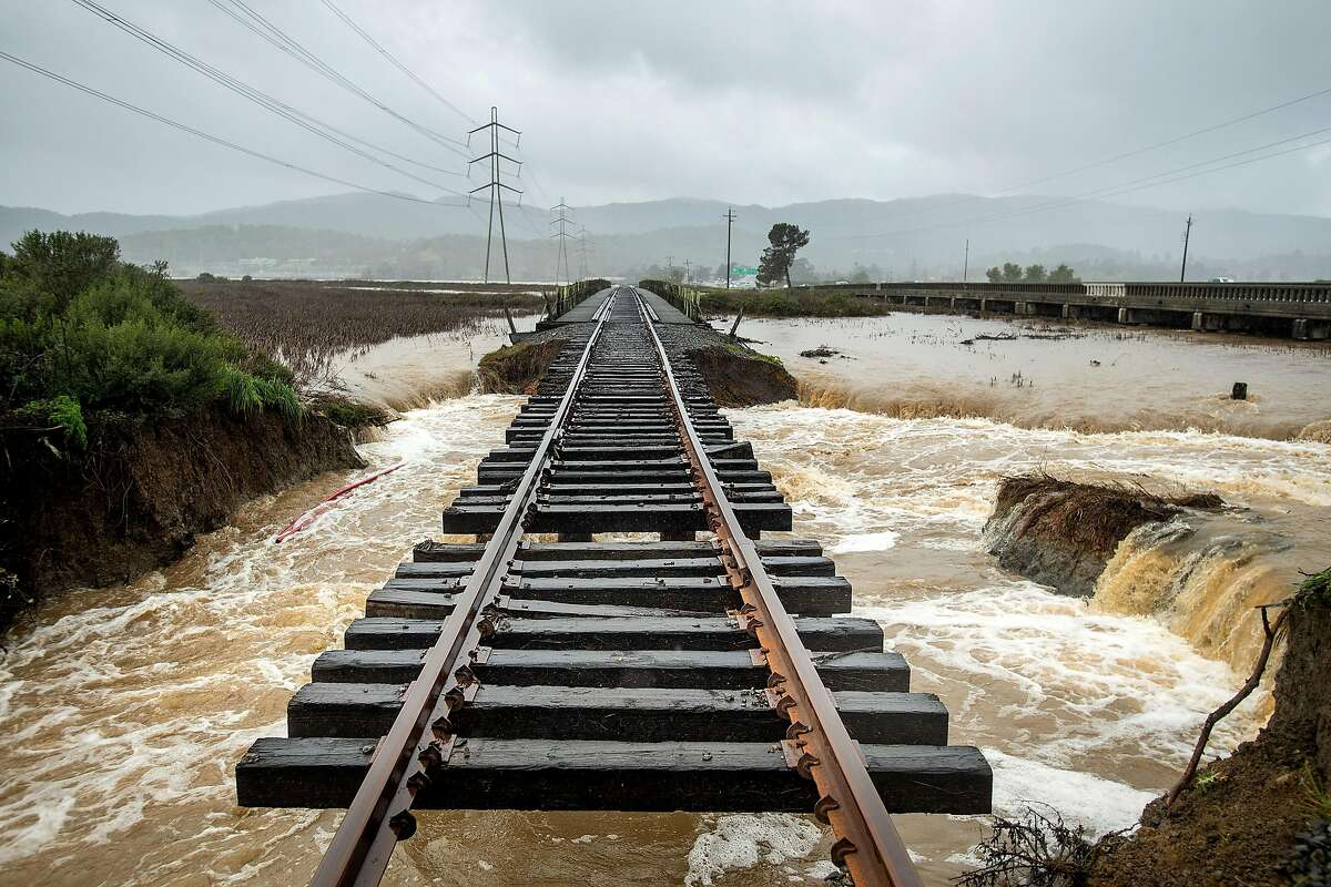 Railroad tracks hang suspended above flood waters following a levee break along highway 37 near Novato, Calif., on Thursday, Feb. 14, 2019. Water from Novato Creek was sent rushing beneath the tracks after the ground below gave way.