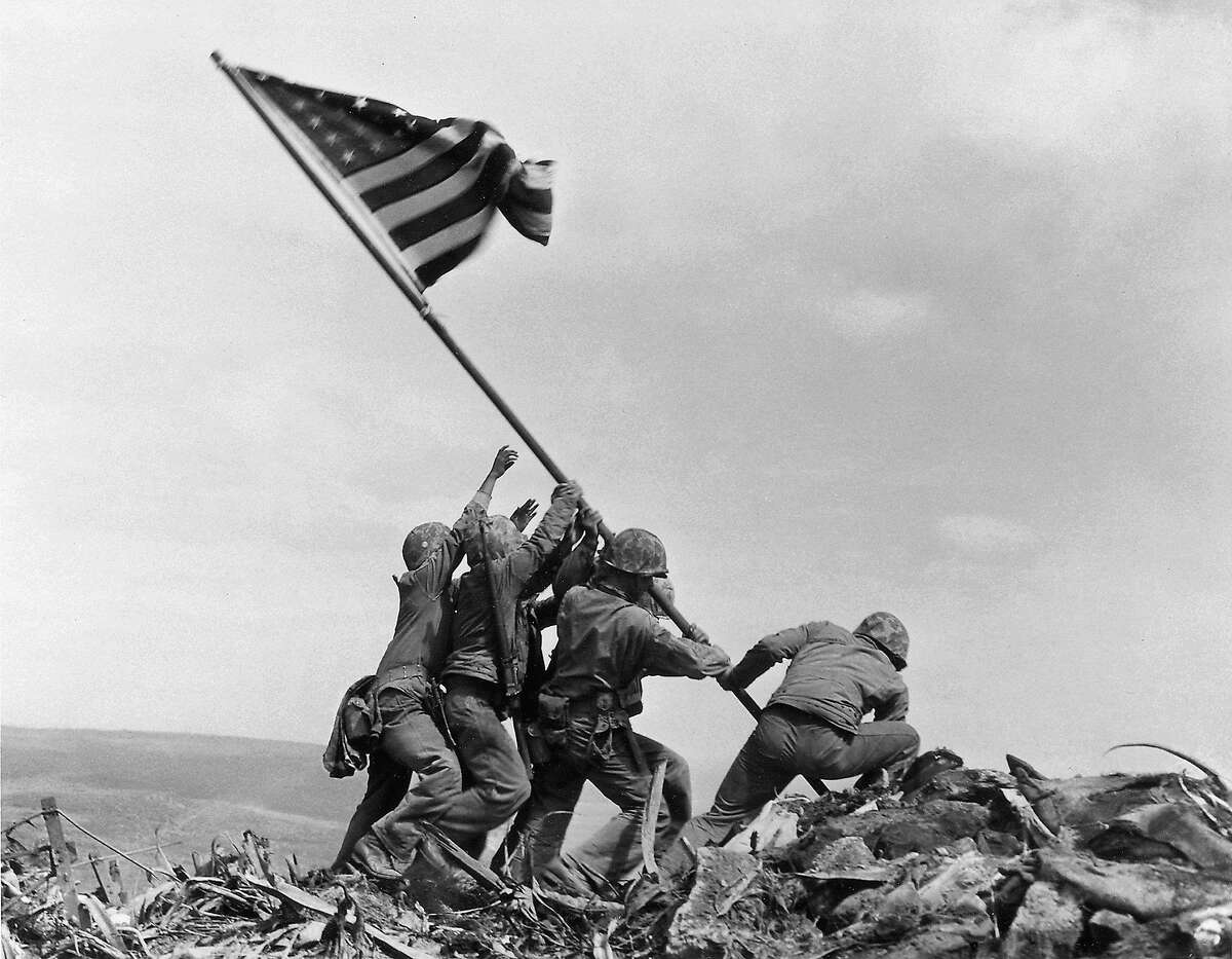 In this Feb. 23, 1945 file photo, U.S. Marines of the 28th Regiment, 5th Division, raise a U.S. flag atop Mount Suribachi, Iwo Jima. Strategically located 660 miles from Tokyo, the Pacific island became the site of one of the bloodiest, most famous battles of World War II against Japan. (AP Photo/Joe Rosenthal, File)