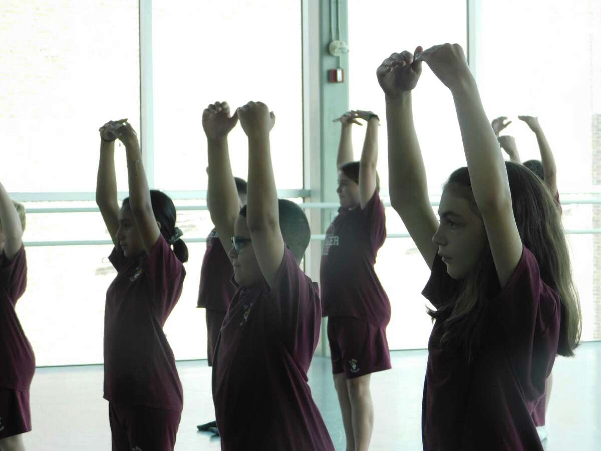 Students from St. John Paul the Great Academy practice stretching exercises at Nutmeg Ballet Conservatory, part of a 10-week collaborative outreach program between the two organizations.