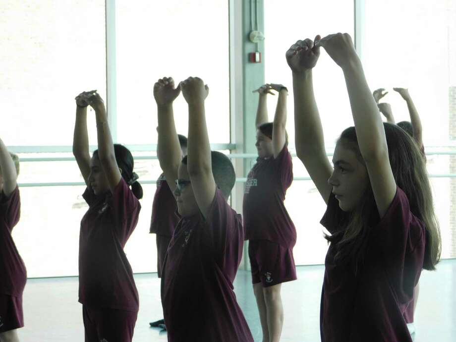 Students from St. John Paul the Great Academy practice stretching exercises at Nutmeg Ballet Conservatory, part of a 10-week collaborative outreach program between the two organizations. Photo: Jack Sheedy / Contributed Photo