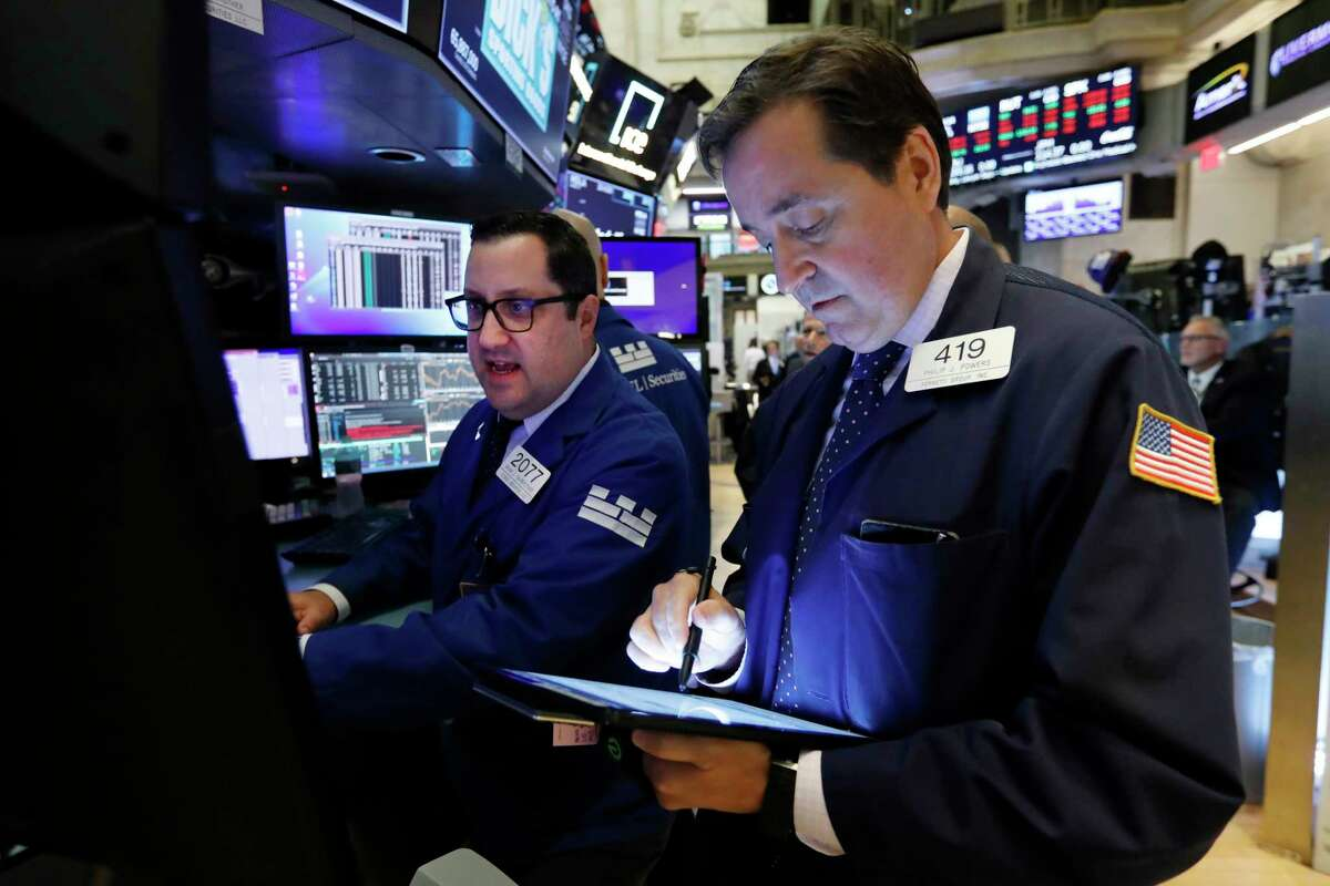 FILE - In this Oct. 8, 2019, file photo specialist Brian Fairbrother, left, and trader Philip Powers work on the floor of the New York Stock Exchange. The U.S. stock market opens at 9:30 a.m. EDT on Thursday, Oct. 17. (AP Photo/Richard Drew, File)