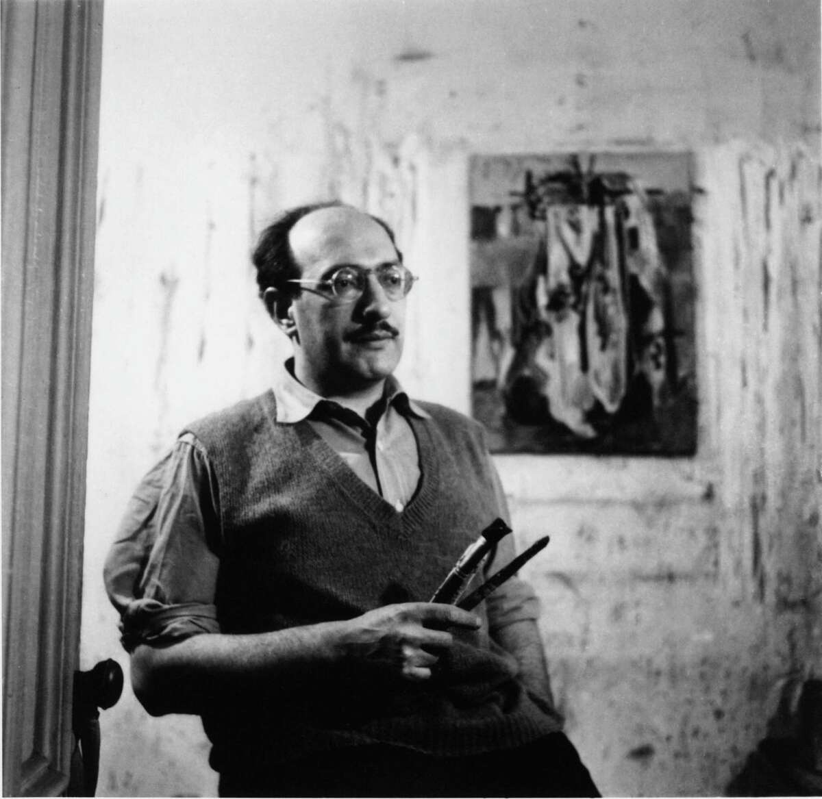 """Mark Rothko holding brushes in front of work on paper Photographer: unknown. Photo featured in the PBS American Masters Documentary """"Rothko: Pictures Must Be Miraculous"""""""