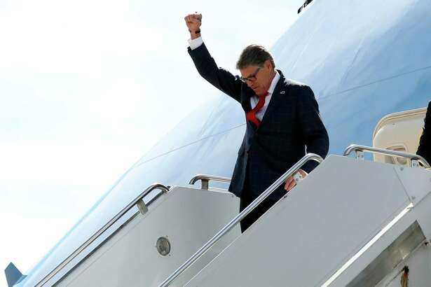 Energy Secretary Rick Perry gestures as he arrives on Air Force One with President Donald Trump at Naval Air Station Joint Reserve Base in Fort Worth. Perry reportedly told Trump he is resigning.