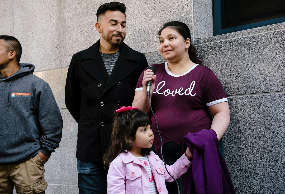 Orland Lopez, left, and Edwin Carmona-Cruz listen as Aida Andrade Amaya, says a few words while holding on to her four year old daughter Jade, during a rally by immigrant rights supporters outside of Immigration and Customs Enforcement's headquarters in San Francisco, California, on Thursday, Oct. 17, 2019. Lawyer Jehan Romero, of Pangea Legal Services filed a lawsuit on behalf of her client Aida Andrade Amaya against Immigration and Customs Enforcement and U.S. Attorney General Willian Barr, arguing that Aida's detention was unjust and illegal after she was kept in ICE detention for several months even after winning her asylum case earlier this year.