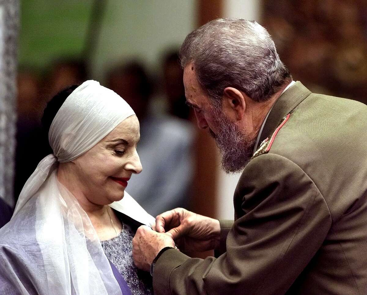 FILE - In this Dec. 20, 2000 file photo, Alicia Alonso, Cuba's grande dame of dance and the founder of the internationally renowned National Ballet of Cuba, receives the Jose Marti medal, Cuba's highest honor, from Cuban leader Fidel Castro, at the Revolution Palace in Havana. Cuba's national ballet has reported that Alonso has died on Thursday, Oct. 17, 2019. (AP Photo/Jose Goitia, File)
