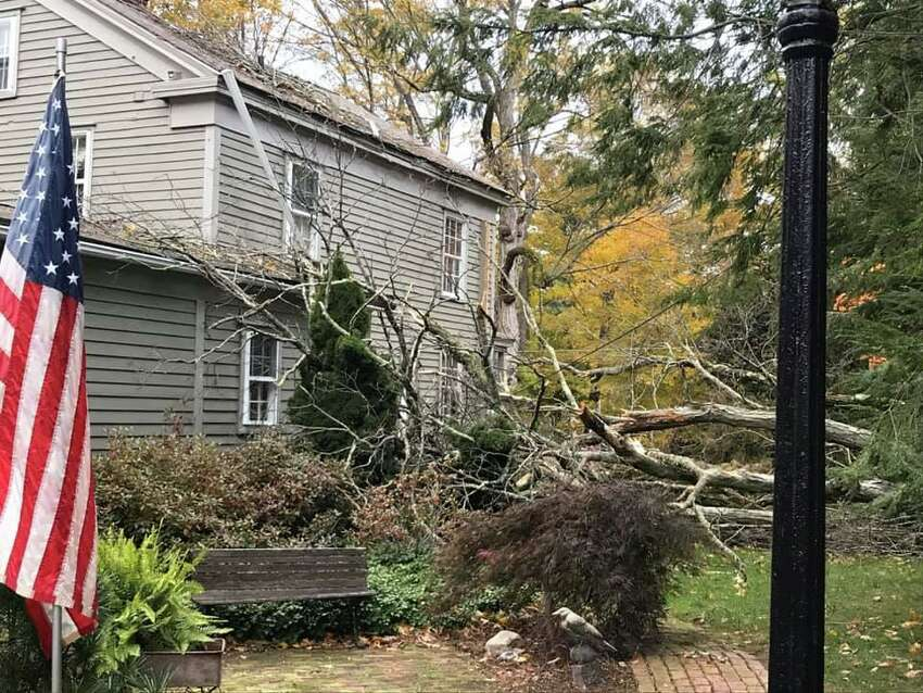 A fallen tree broke two glass windows on the side of a Wilton Road East home in Ridgefield on Wednesday, October 16.