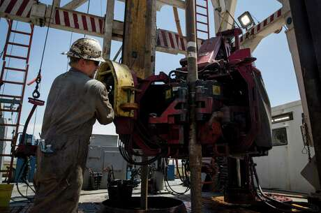 "Caleb Adair, a floorhand from Booneville, Ark., builds stands on a drilling rig on Friday, Aug. 23, 2019, near Malaga, N.M. The task consists of joining together three sections of pipe, called ""joints."""