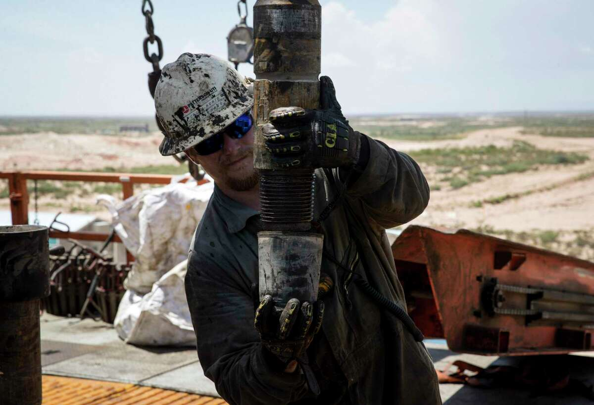 """Caleb Adair, a floorhand from Booneville, Ark., builds stands on a drilling rig on Friday, Aug. 23, 2019, near Malaga, N.M. The task consists of joining together three sections of pipe, called """"joints."""""""