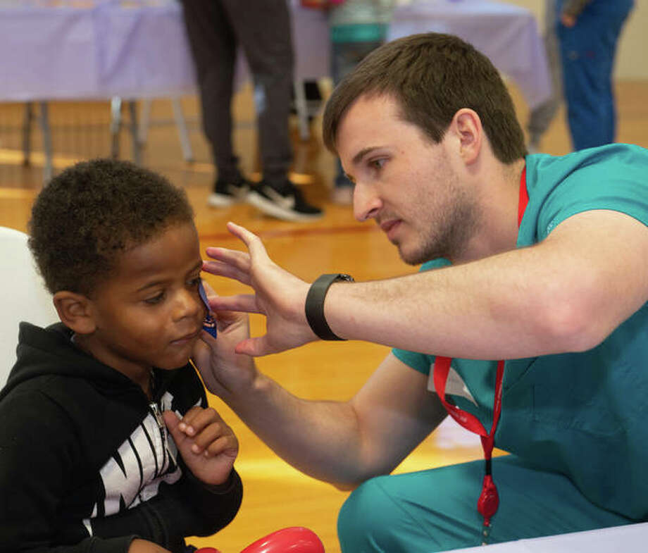 First-year SIU SDM student Grant Russell face paints a young patient at the annual Give Kids A Smile Day Monday. This year's program saw 85 children and provided more than $53,000 in free services.