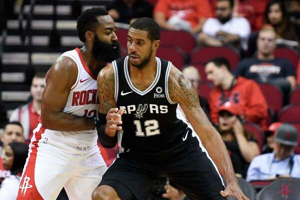San Antonio Spurs center LaMarcus Aldridge (12) is defended by Houston Rockets guard James Harden during the first half of an NBA preseason basketball game Wednesday, Oct. 16, 2019, in Houston. (AP Photo/Eric Christian Smith)