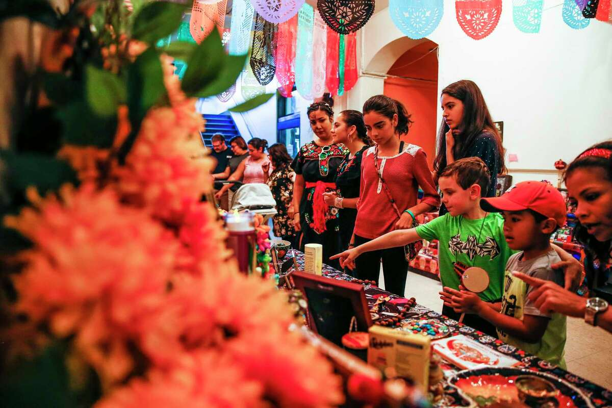 People look at altars at the Multicultural Education and Counseling through the Arts' annual Día De Los Muertos Festival in Houston last year. A reader believes Día de Los Muertos has been reduced to a Fiesta-like celebration.