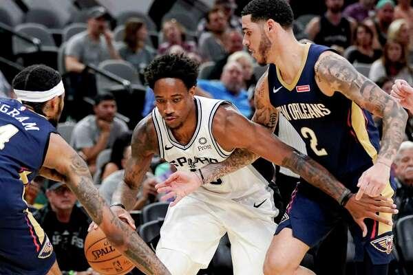San Antonio Spurs' DeMar DeRozan, center, drives between New Orleans Pelicans' Brandon Ingram, left, and Lonzo Ball during the second half of an NBA preseason basketball game, Sunday, Oct. 13, 2019, in San Antonio. (AP Photo/Darren Abate)