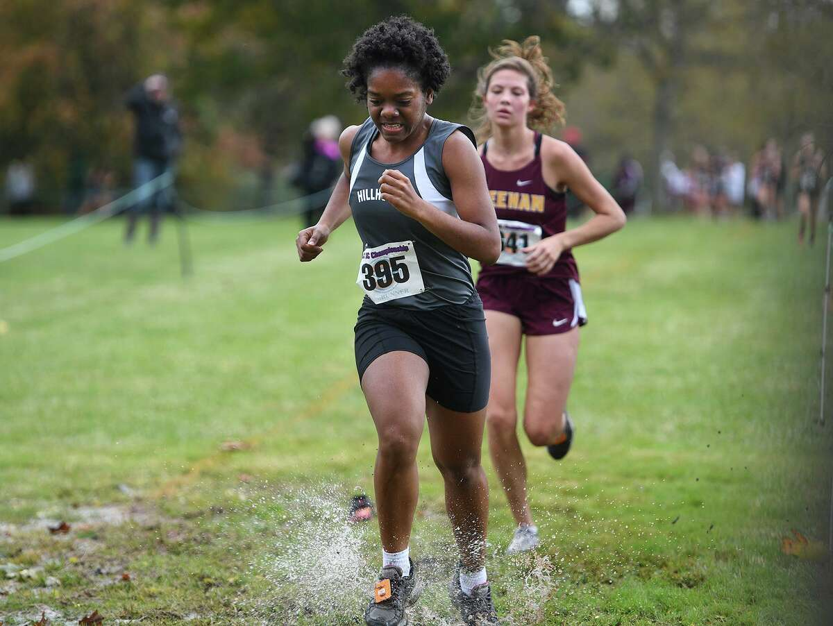 Hillhouse's Sharmaine Donaldson splashes through flooded grass on the way to the finish at the SCC Cross Country Championships at East Shore Park in New Haven, Conn. on Thursday, October 17, 2019.