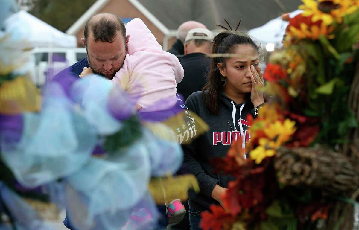 Carrying his almost 2-year-old daughter, Avery, Luke Foster and his wife, Carmen Foster, of Floresville, Texas, pay their respects at a memorial for the Sutherland Springs, Texas First Baptist Church victims, Wednesday, Nov. 8, 2017. On Sunday, Devin Patrick Kelley, 26, walked in on worshippers and killed 26 women, children and men, injuring dozens others.