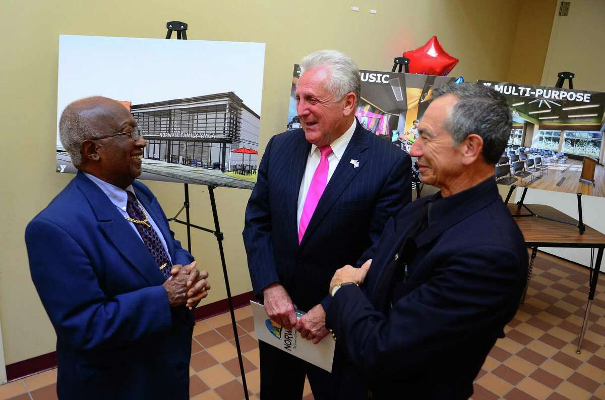 Norwalk Mayor Harry W. Rilling, center, chats with District B Democratic Party Chair Bobby Burgess after the mayor annouced a proposal for a new state-of-the-art community center to be built during a press conference at the present South Norwalk Community Center in South Norwalk, Conn., on Thursday Oct. 17, 2019. At right is Norwalk Police Department's Community Police Officer Cesar Ramirez.
