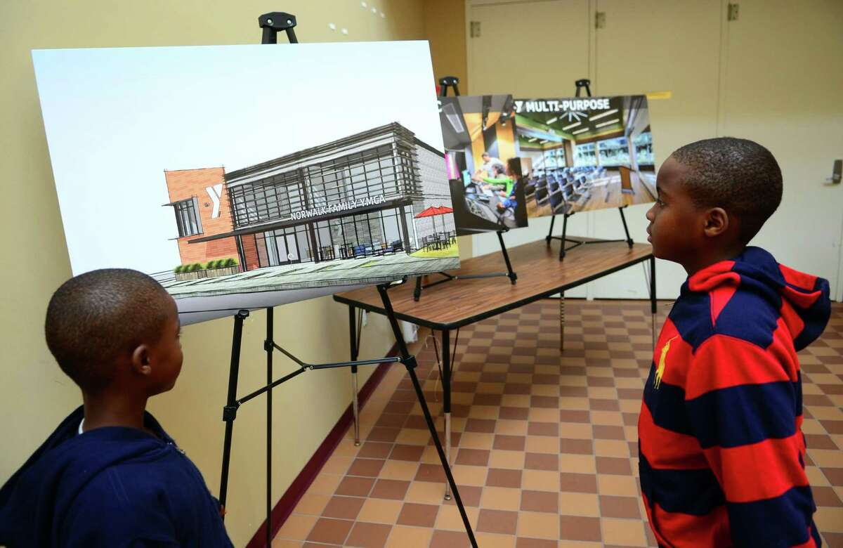 Silas Jefferson, 9, right, and his brother Caleb, 8, check out a photo of a proposed new state-of-the-art community center to be built during a news conference held by Norwalk Mayor Harry Rilling at the present South Norwalk Community Center on Thursday.