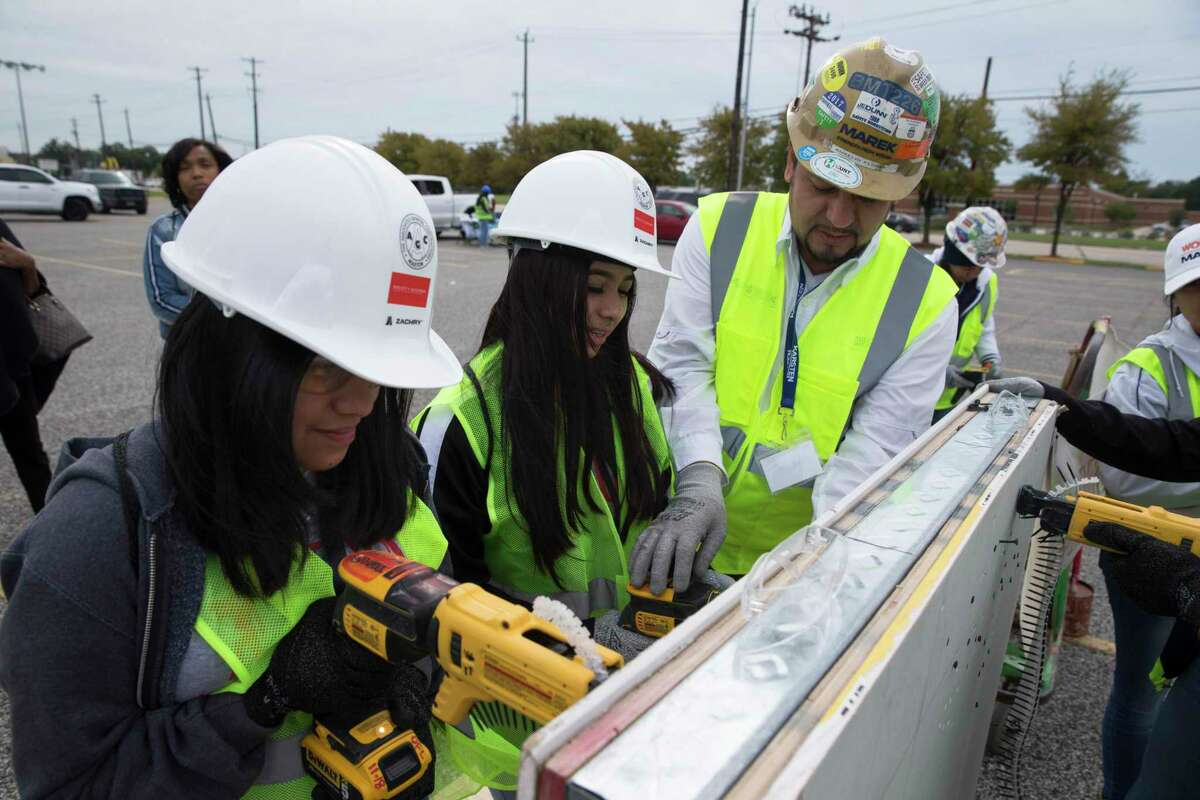 Aurelio Flores, of Marek Brothers Company, teaches MacArthur High School ninth-graders Nayeli Guzman, left, and Yeferly Orozco how to put a nail in the drywall at M.O. Campbell Educational Center on Thursday, Oct. 17, 2019, in Houston. More than 1,000 girls from the Aldine ISD participated in She Builds Houston, a conference for middle and high school students aimed at encouraging girls to join the construction industry.