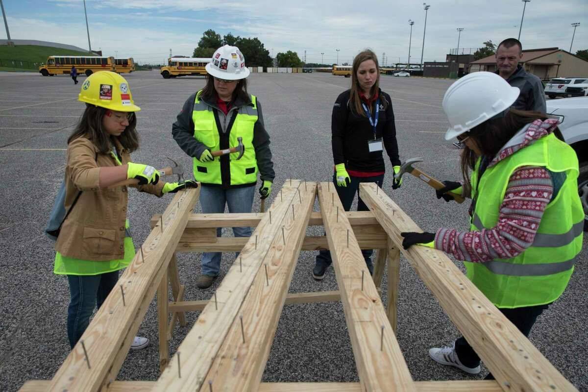 Aldine ISD high school students Evelyn Rojas, left, and Cristal Pineda, right, hammer nailes into wood panels at M.O. Campbell Educational Center on Thursday, Oct. 17, 2019, in Houston. More than 1,000 girls from the school district participated in She Builds Houston, a conference for middle and high school students aimed at encouraging girls to join the construction industry.