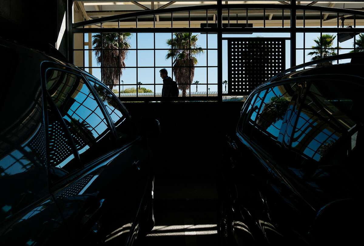 A pedestrian walks by the BART Millbrae Station parking structure in Millbrae, Calif. on Thursday, October 16, 2019. BART is preparing to launch an ambitious plan which will see much of the transit agency's dedicated parking lots shrunken or eliminated to become sites of high-density housing.