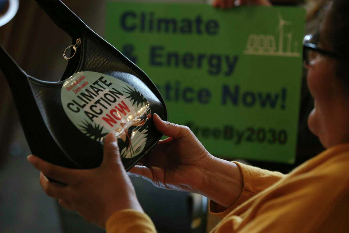 Molly Wright places a sticker on her purse showing support for the Climate Action and Adoption Plan. The San Antonio City Council voted 10-1 to approve the plan on Thursday, Oct. 17, 2019. The lone vote against it was cast by District 10 Councilmember Clayton Perry.