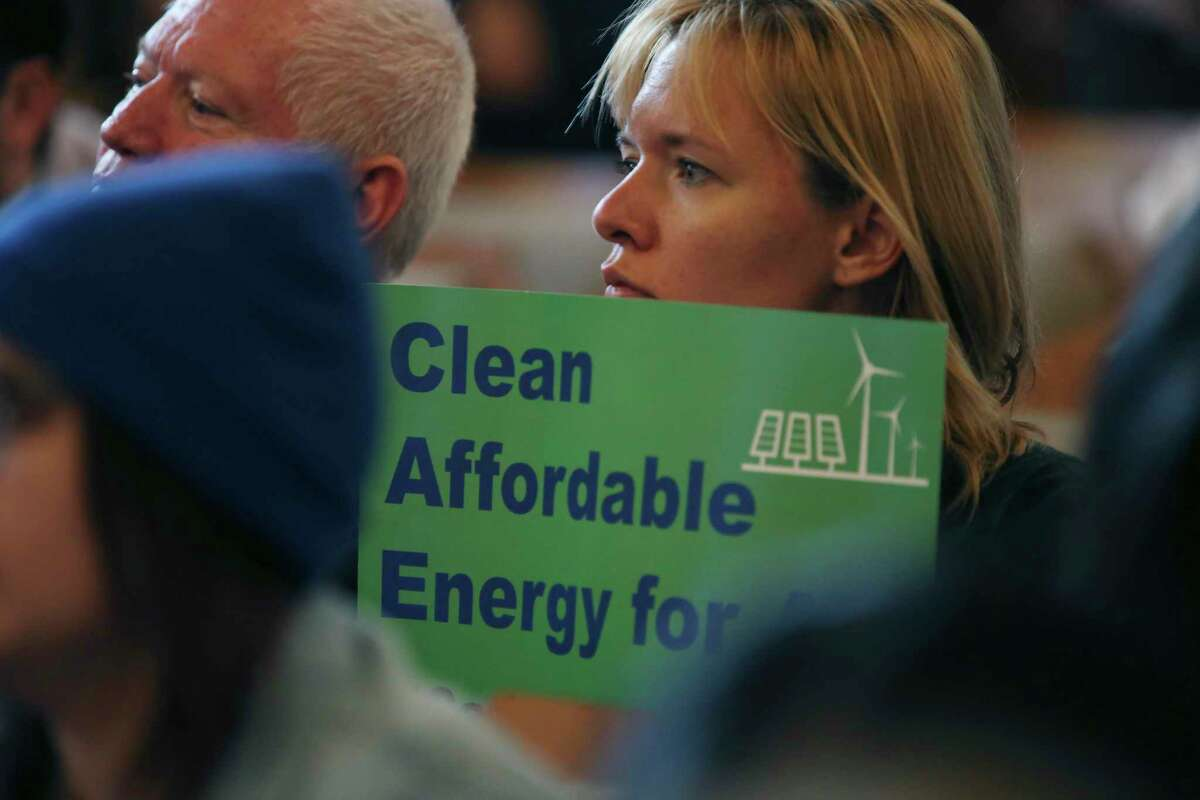Supporters hold signs before the San Antonio City Council votes 10-1 in favor of the Climate Action and Adaptation Plan on Thursday, Oct. 17, 2019.