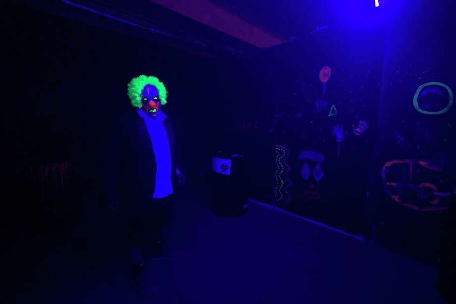 Conroe Fire Department engine operator David Thompson walks toward an entrance dressed as a toxic clown Tuesday, October 8, 2019 in The House Of Fear in Conroe. The Conroe Professional Firefighters Foundation is hosting the haunted house to raise money for its benevolence fund. House of Fear will be open Photo: Cody Bahn, Houston Chronicle / Staff Photographer / © 2019 Houston Chronicle